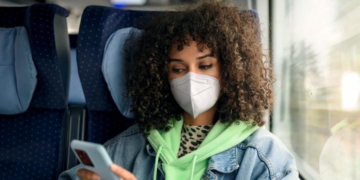Junge Frau mit FFP2-Maske entspannt im ICE