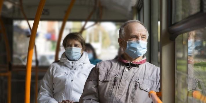 Rentner mit medizinischer Gesichtsmaske sitzt im Bus