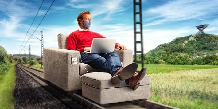 Mann in Sessel auf Schiene mit Mundschutz