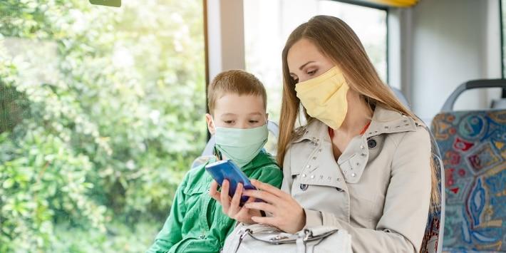 Frau mit ihrem Sohn im Bus während Coronavirus-Krise