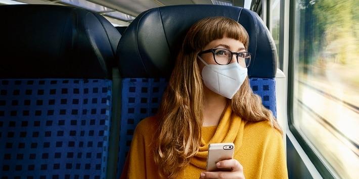 Frau im Regiozug mit FFP2-Maske
