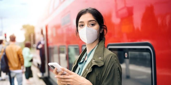 Pendlerin mit FFP2-Maske und Tasche und Smartphone vor einem Regionalzug