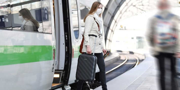 Woman with luggage leaving a train