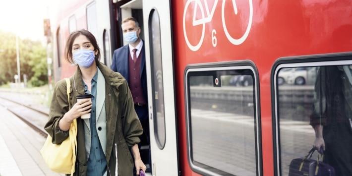 Pendlerin mit Arbeitstasche geht mit Coffee-to-Go-Becher am Zug entlang.