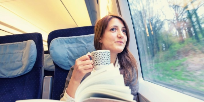A young woman drinking coffee inside a running train