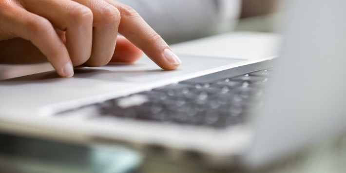 Woman using laptop indoor. close-up hand