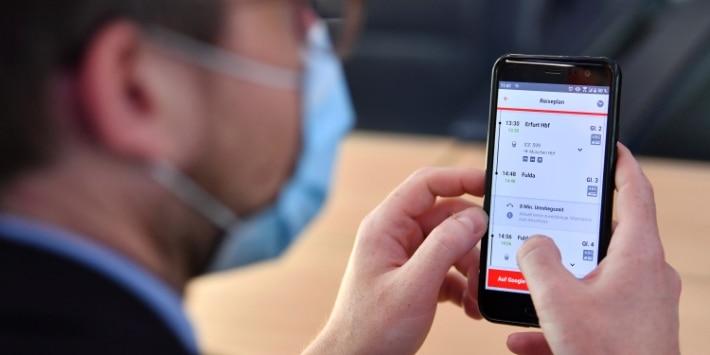 Geschäftsreisender mit Mund-Nase-Bedeckung im ICE nutzt den DB Navigator auf seinem Smartphone