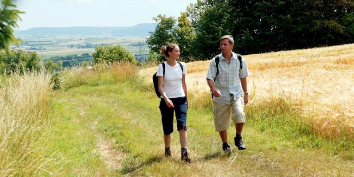 Mann und Frau wandern auf einer Wiese am Feld