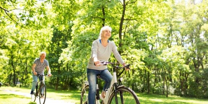 Mann und Frau auf Fahrrädern auf einer waldigen Wiese