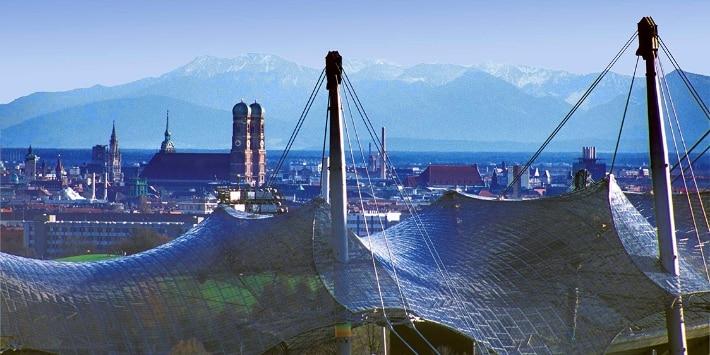 Blick über das Olympiazelt-Dach auf München und die Berge