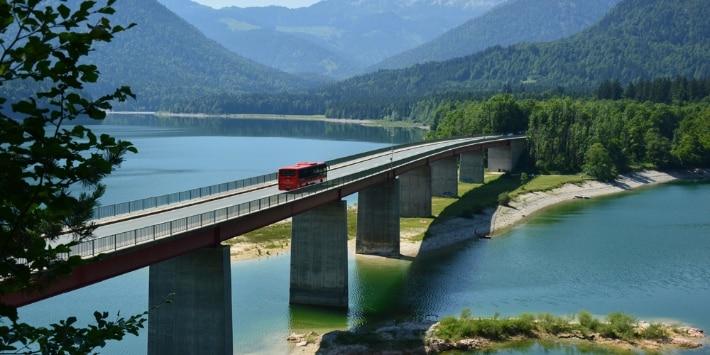Roter DB-Bus fährt über eine Brücke vor Bergen und See