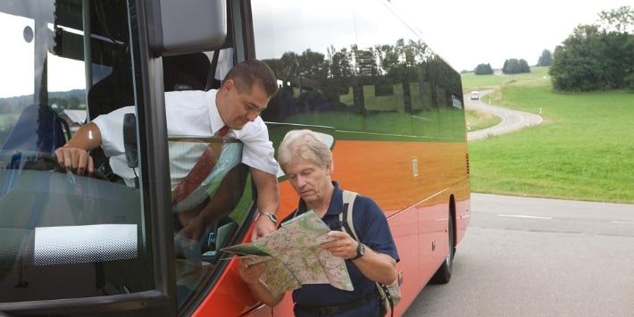 Busfahrer hilft Wanderer mit Karte