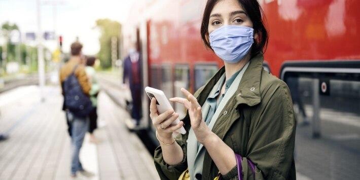 Frau am Bahnsteig checkt ihr Smartphone