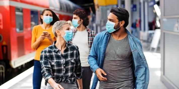 Personen mit medizinischer Maske am Bahnsteig Regionalzug