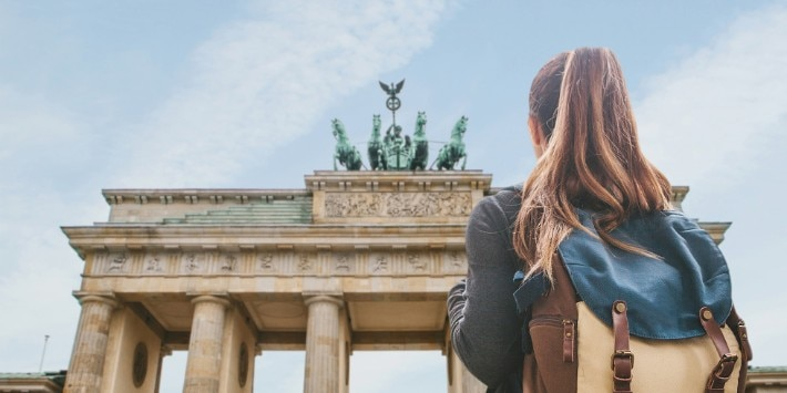 A tourist girl with a backpack looking at the Brandenburg Gate in Berlin