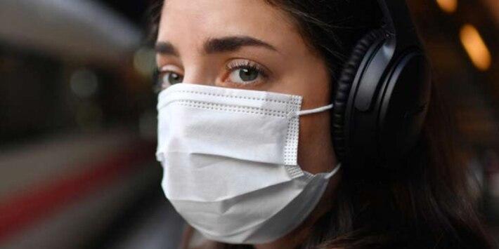 Frau mit medizinischer Maske und Kopfhörern ICE