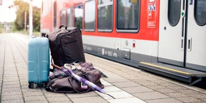 Gepäck am Bahnsteig, Regio-Zug im Hintergrund