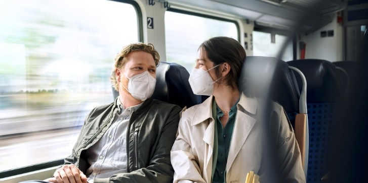 Pendler-Pärchen im Regionalzug mit FFP2-Masken