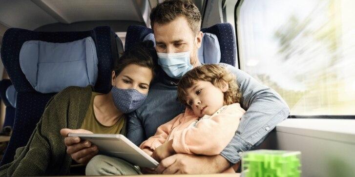 Familie sitzt im ICE und nutzt ein Tablet.