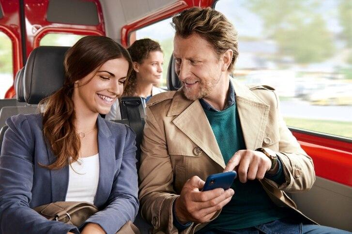Paar mit Handy im Bus
