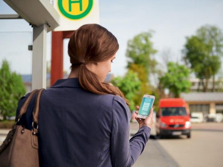 Frau mit Smartphone an der Bushaltestelle