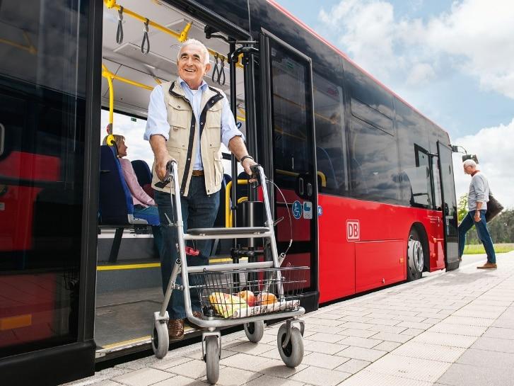 Senior steigt mit Rollator hinten aus Bus aus