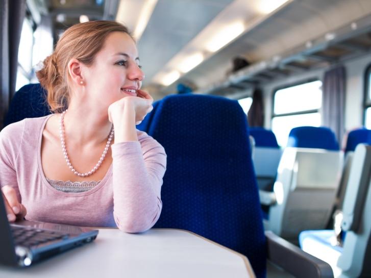 Jonge vrouw in trein met laptop