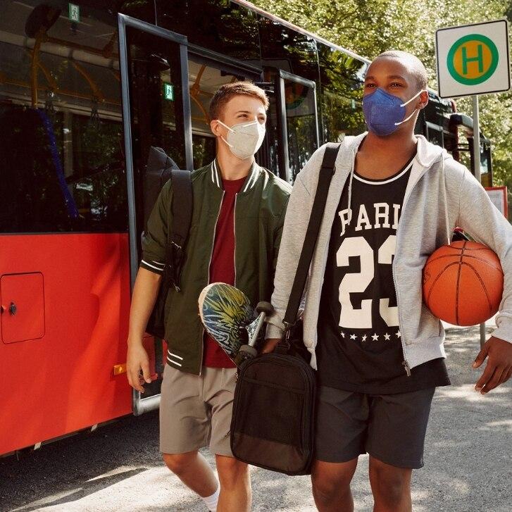 Junge Männer mit Basketbällen vor Bus