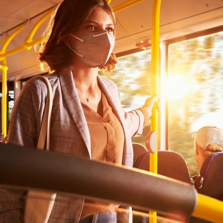 Frau mit Maske im sonnigen Bus