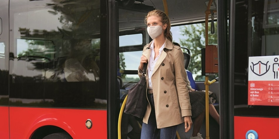 Frau mit Maske steigt aus Bus