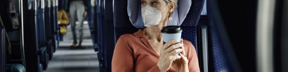 Seniorin mit Mehrwegkaffeetasse sitzt im ICE Abteil.