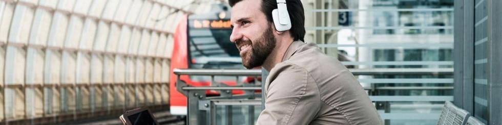 Mann mit Kopfhörer am Bahnsteig