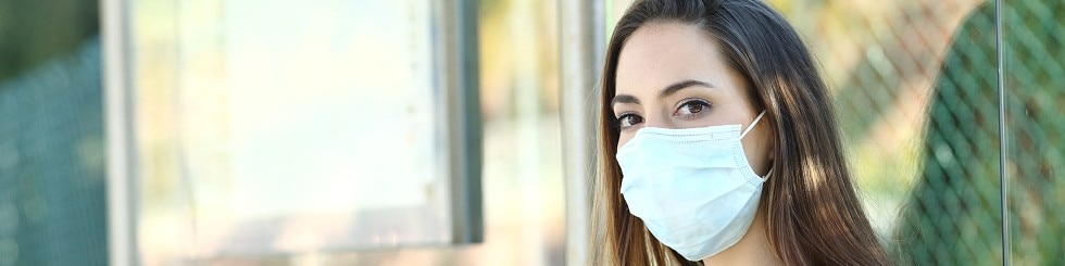 Frau trägt Maske, um Ansteckung in einer Bushaltestelle zu verhindern