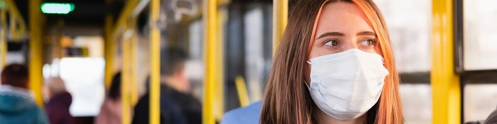 Junge Erwachsene pendeln mit einer schützenden Gesichtsmaske. Coronavirus.