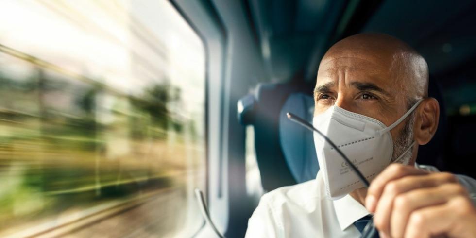 Ein Geschäftsreisender blickt nachdenklich durchs Fenster, hält Brille in der Hand.