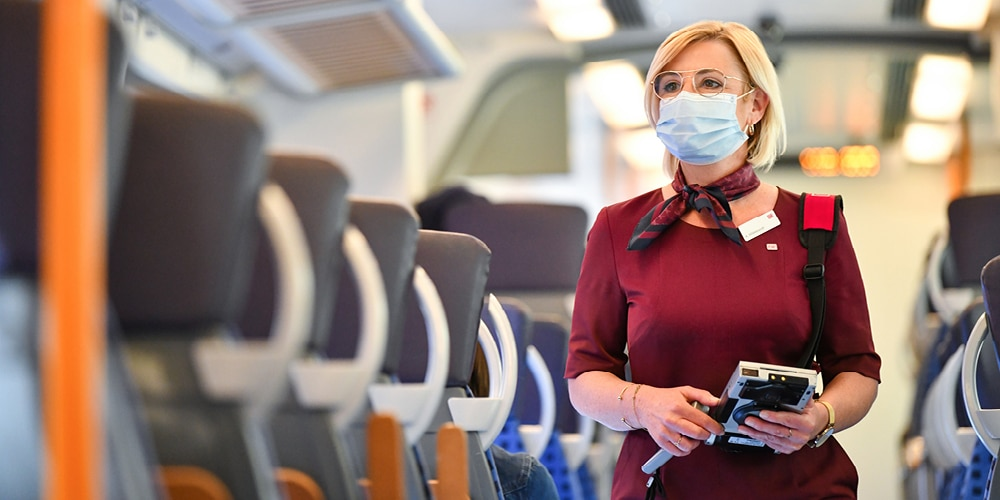 Zugbegleiterin mit medizinischer Maske