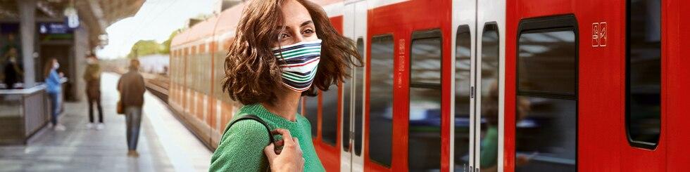 Frau am Bahnsteig mit Maske