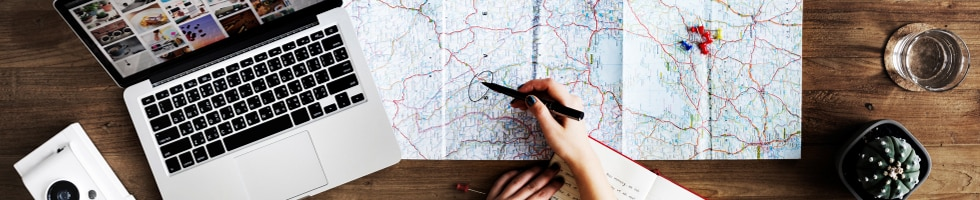 Travel planning with map, laptop and notebook