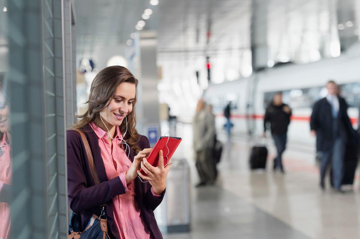 Frau mit Tablet am Bahnsteig
