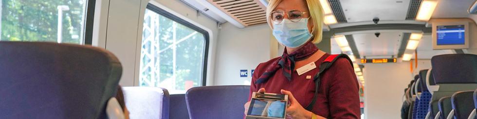 Zugbegleiterin mit Mund-Nase-Bedeckung