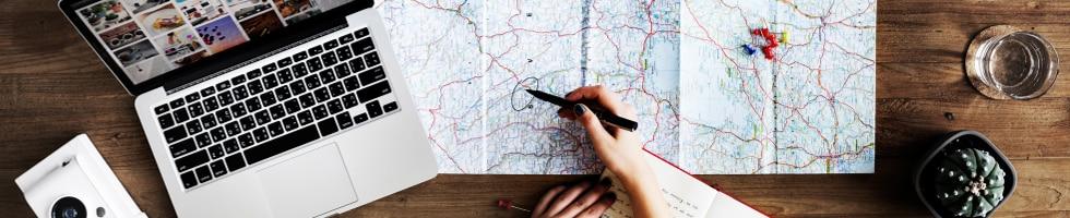 Planificación de un viaje con mapa, ordenador portátil y bloc de notas