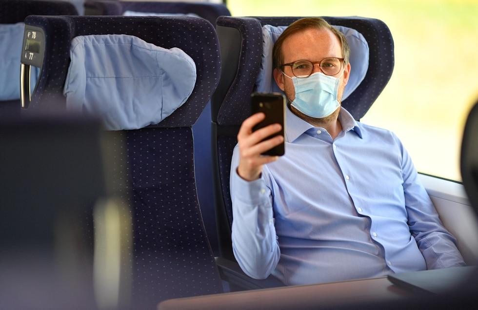 Reisende mit Mund-Nase-Bedeckung