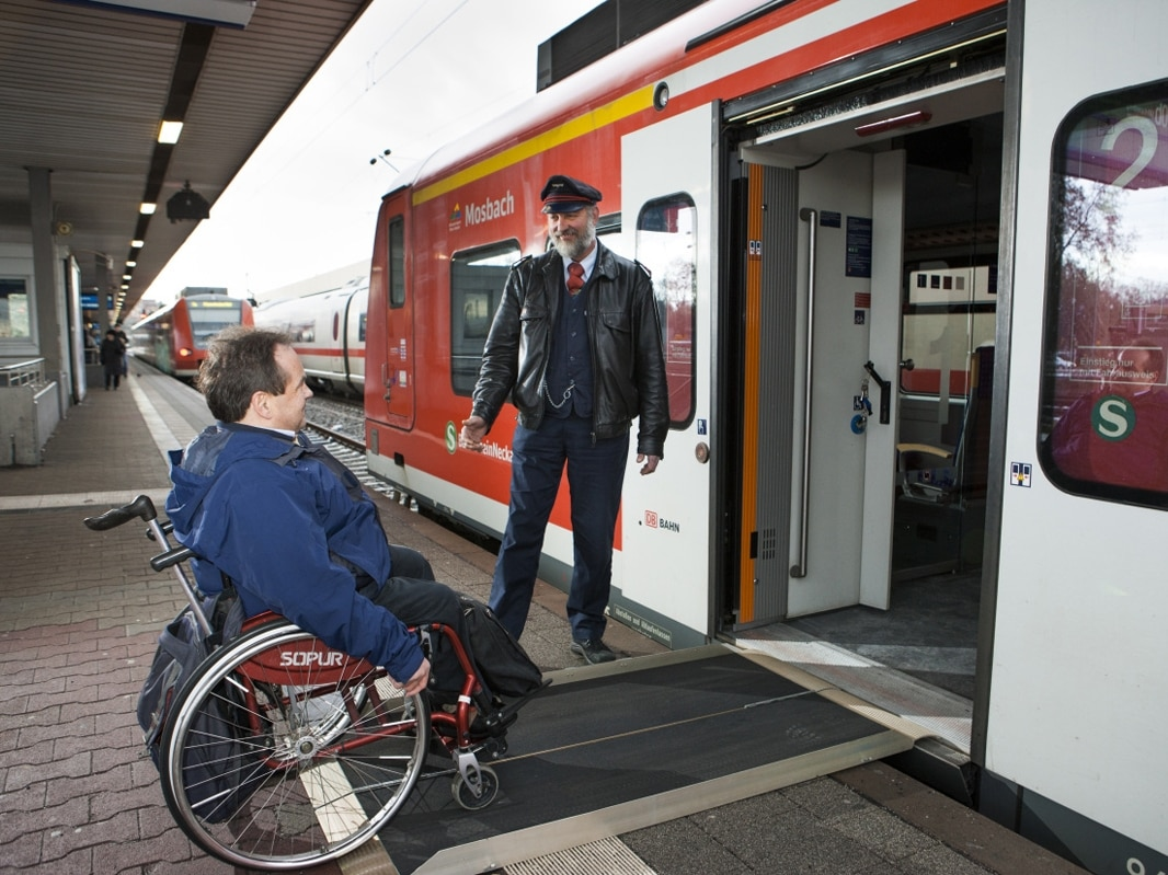 Rollstuhlfahrer steigt über Rampe in den Zug ein